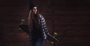 Muchacha del inconformista en vidrios con un longboard Foto de archivo