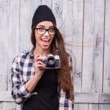 Muchacha del inconformista en vidrios y gorrita tejida negra con la cámara del vintage Imagenes de archivo