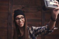 Muchacha del inconformista en vidrios y gorrita tejida negra con la cámara del vintage Imagen de archivo