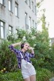 Muchacha del inconformista que baila a la música en auriculares Fotos de archivo libres de regalías