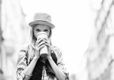 Muchacha del inconformista que bebe la bebida caliente en la calle de la ciudad Imagen de archivo libre de regalías