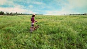 Muchacha del inconformista que camina con la bicicleta en verano Imagen de archivo libre de regalías