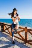 Muchacha del inconformista que charla en el teléfono elegante que descansa en la costa Foto de archivo libre de regalías