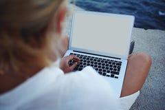 Muchacha del inconformista que comprueba el correo electrónico en el ordenador portátil mientras que se sienta cerca del mar en d Foto de archivo libre de regalías