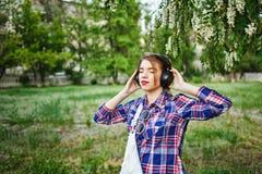Muchacha del inconformista que disfruta de música en los auriculares Fotografía de archivo