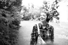 Muchacha del inconformista que disfruta de música en los auriculares y la sonrisa Fotografía de archivo