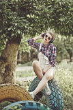 Muchacha del inconformista que escucha la música con los auriculares en el parque i del verano Imagen de archivo libre de regalías