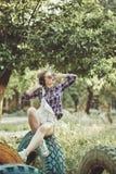 Muchacha del inconformista que escucha la música con los auriculares en parque del verano Fotografía de archivo libre de regalías