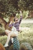 Muchacha del inconformista que escucha la música con los auriculares en un parque del verano Fotos de archivo libres de regalías