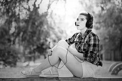 Muchacha del inconformista que escucha la música en los auriculares Fotos de archivo