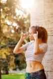 Muchacha del inconformista que escucha la música en los auriculares en la puesta del sol Fotografía de archivo