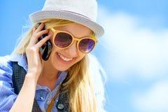 Muchacha del inconformista que habla el teléfono móvil contra el cielo Imagen de archivo libre de regalías