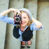 Muchacha del inconformista que hace la foto con la cámara retra en la calle de la ciudad Imagen de archivo