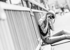 Muchacha del inconformista que hace la foto con la cámara retra mientras que se sienta en el CIT Imágenes de archivo libres de regalías