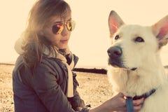 Muchacha del inconformista que juega con el perro en una playa durante puesta del sol, llamarada fuerte de la lente imagen de archivo libre de regalías