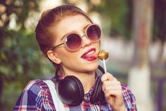 Muchacha del inconformista que lame la piruleta Auriculares Fotografía de archivo libre de regalías