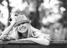 Muchacha del inconformista que se sienta en banco en el parque Fotografía de archivo libre de regalías