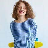 Muchacha del inconformista que sostiene un monopatín vivo del color Fotos de archivo