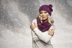 Muchacha del invierno en blanco con el sombrero y la bufanda púrpuras Foto de archivo