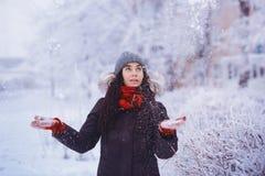Muchacha del invierno en guantes rojos y nieve que sopla de la bufanda Belleza Girl modelo adolescente alegre que se divierte en  Foto de archivo