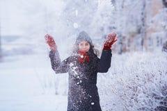 Muchacha del invierno en guantes rojos y nieve que sopla de la bufanda Belleza Girl modelo adolescente alegre que se divierte en  Imagen de archivo