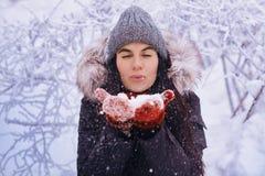 Muchacha del invierno en guantes rojos y nieve que sopla de la bufanda Belleza Girl modelo adolescente alegre que se divierte en  Fotos de archivo libres de regalías