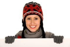 Muchacha del invierno que lleva a cabo la muestra en blanco Fotos de archivo