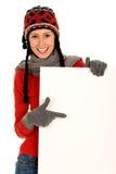 Muchacha del invierno que lleva a cabo la muestra en blanco Imagen de archivo libre de regalías