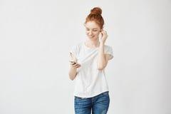 Muchacha del jengibre con las pecas en auriculares que sonríe mirando el teléfono Foto de archivo libre de regalías
