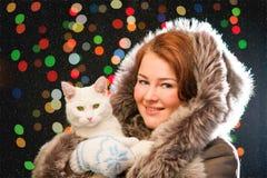 Muchacha del jengibre en manoplas que llevan del abrigo de pieles con el gato Imagenes de archivo