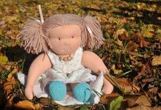 Muchacha del juguete en las hojas de otoño Imagenes de archivo