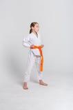 Muchacha del karate en kimono en soporte en el fondo del estudio Foto de archivo