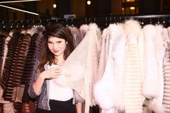 Muchacha del modelo de moda del adolescente en tienda del sitio de la demostración del abrigo de pieles Foto de archivo