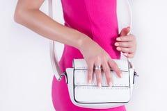 Muchacha del modelo de moda con el bolso blanco a disposición y el vestido rosado imágenes de archivo libres de regalías
