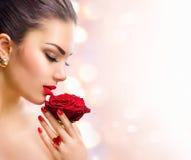 Muchacha del modelo de moda con la rosa del rojo en su mano Fotos de archivo