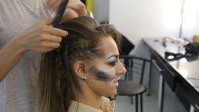 Muchacha del modelo de moda en peluqueros trabajo de la mano del peluquero sobre el pelo del cliente almacen de video