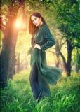 Muchacha del modelo de moda de la belleza que presenta sobre los árboles florecientes, disfrutando de la naturaleza en manzanar d fotos de archivo