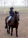 Muchacha del montar a caballo en la niebla Foto de archivo