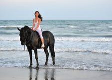 Muchacha del montar a caballo en una playa Imagenes de archivo