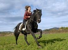 Muchacha del montar a caballo y semental negro Fotos de archivo libres de regalías
