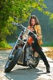 Muchacha del motorista en una motocicleta Fotos de archivo libres de regalías