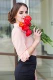 Muchacha del negocio con el ramo de tulipanes rojos Imagen de archivo libre de regalías
