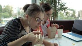 Muchacha del negocio de dos jóvenes para el almuerzo que come los tallarines chinos y que bebe el café, en vista del desarrollo d almacen de metraje de vídeo
