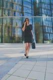 Muchacha del negocio en un vestido negro que habla en el teléfono en el bolso Imágenes de archivo libres de regalías