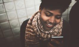 Muchacha del negro de Loveley que charla vía smartphone Fotografía de archivo libre de regalías