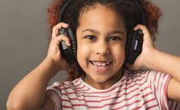 Muchacha del niño del Afro en auriculares grandes en el fondo gris del estudio fotografía de archivo libre de regalías