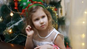 Muchacha del niño antes de Papá Noel y un regalo en la Navidad Año Nuevo y árbol de navidad almacen de metraje de vídeo