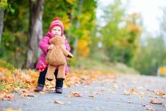 Muchacha del niño con el oso de peluche al aire libre Imagen de archivo libre de regalías