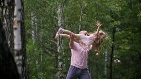 Muchacha del niño con el padre en parque - el papá está haciendo girar a su niña, a cámara lenta