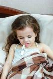 Muchacha del niño con el thermomert de medición del whith del temrerature de la fiebre en boca fotografía de archivo libre de regalías
